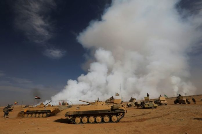 Iraqi army tanks gather after the liberation of a village from Islamic State militants, south of Mosul.