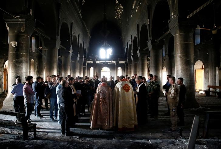 Iraqi priests hold the first Sunday mass at the Grand Immaculate Church since it was recaptured from Islamic State in Qaraqosh, near Mosul