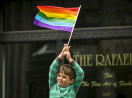 A young boy waves a rainbow flag while watching the San Francisco gay pride parade