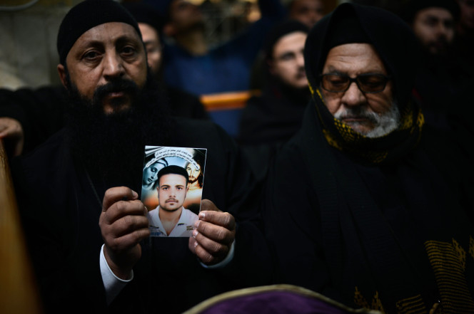 A Coptic clergyman shows a picture of a man whom he says is one of the Egyptian Coptic Christians purportedly murdered by Islamic State group militants