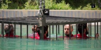 Captives inside a metal cage are lowered into a deep pool after they were condemned to die by an ISIS court for collaborating with enemy forces in Mosul.
