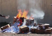 "An Islamic State militant tosses Christian textbooks into a bonfire on the grounds that they are the ""books of infidels"" on March, 10 2016"