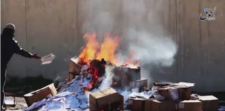 """An Islamic State militant tosses Christian textbooks into a bonfire on the grounds that they are the """"books of infidels"""" on March, 10 2016"""