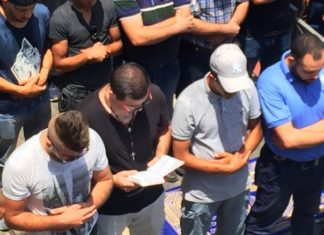 Nidal Aboud, a Christian, holds a Bible and prays beside Muslims in Jerusalem, where there recently have been clashes between Israeli forces and Palestinians.