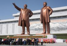 North Koreans bow to the statue of their late supreme leaders Kim Il-sung and Kim Jong-il