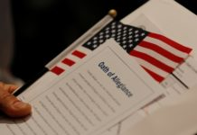 A new United States citizen holds a U.S. flag and a copy of the Oath of Allegiance during a citizenship ceremony at the John F. Kennedy Presidential Library in Boston, Massachusetts, U.S. February 8, 2017. REUTERS