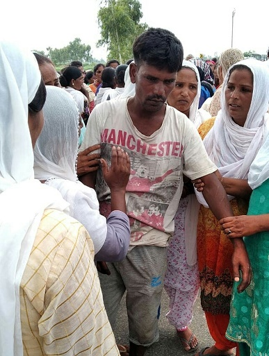 Anjali Masih's father is comforted by local women (World Watch Monitor)