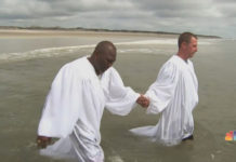 Former KKK grand dragon Ken Parker (R) being baptized in the Atlantic Ocean in July 2018