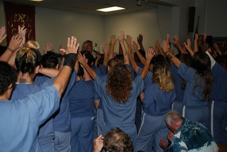 Dawn Knighton leads a group of inmates in prayer.