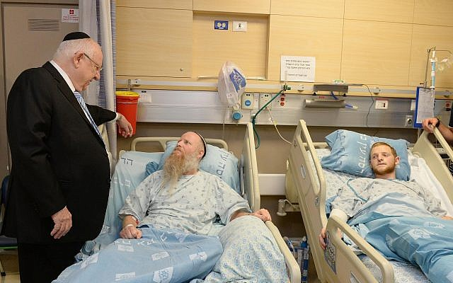 President Reuven Rivlin visits Rabbi Eitan Shnerb, whose daughter Rina was killed in a West Bank terror bombing, and his son Dvir at Hadassah Hospital Ein Kerem in Jerusalem on August 26, 2019.