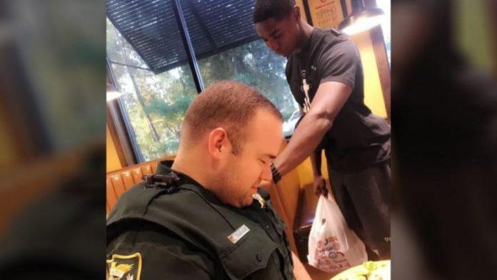 Young man praying over Florida police deputy