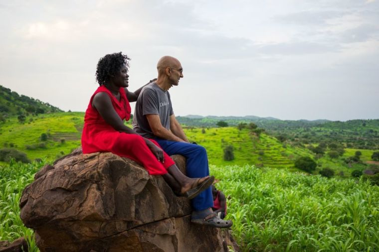 Dr. Tom Catena and his wife, Nasima Mohammed Bashir, sit on a rock in the Nuba Mountains of Sudan. | African Mission Healthcare