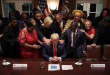 African American supporters lay their hands on U.S. President Donald Trump as they pray for him at the conclusion of a news conference and meeting in the Cabinet Room at the White House February 27, 2020 in Washington, DC.