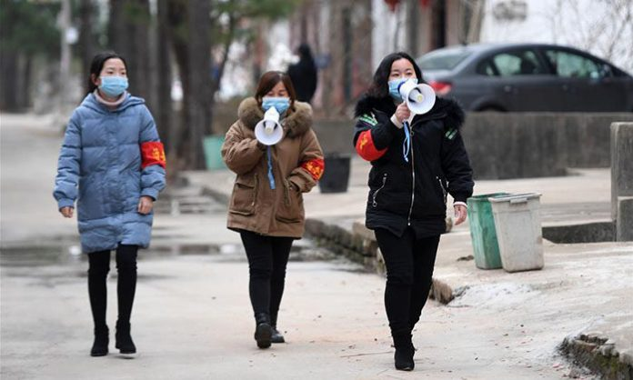 Staff give information on the prevention and control of the novel coronavirus in Hantang Village in Nanchang County, east China's Jiangxi Province, Feb. 3, 2020. Photo: (Xinhua/Wan Xiang)