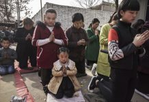 """Chinese Catholic worshippers kneel and pray during Palm Sunday Mass during the Easter Holy Week at an """"underground"""" or """"unofficial"""" church on April 9, 2017 near Shijiazhuang, Hebei Province, China."""