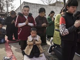 "Chinese Catholic worshippers kneel and pray during Palm Sunday Mass during the Easter Holy Week at an ""underground"" or ""unofficial"" church on April 9, 2017 near Shijiazhuang, Hebei Province, China."
