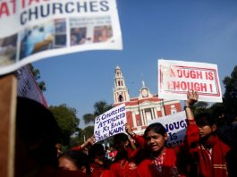 Demonstrators shout slogans as they hold placards during a protest outside a church in New Delhi, India, February 5, 2015.