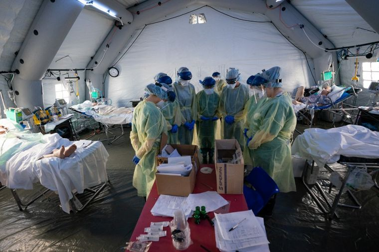 Samaritan's Purse team members pray for COVID-19 patients in the Intensive Care Unit of the Emergency Field Hospital.
