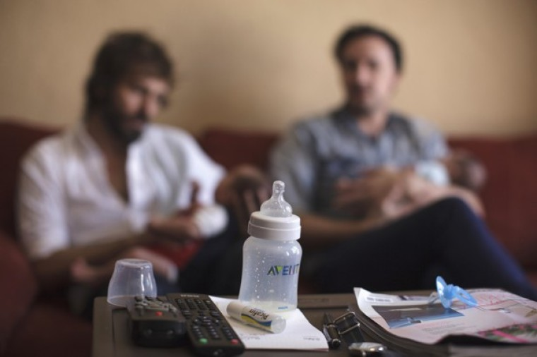 Luis Delgado (L) holds son Marco as husband Antonio Ferndandez holds their daughter Olivia, at their home in Cancun February 24, 2015.